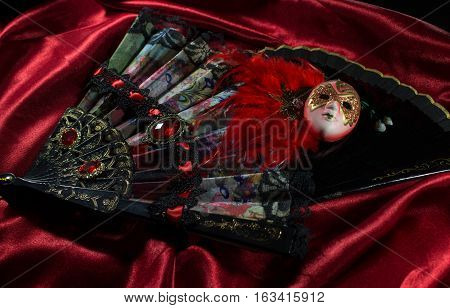 Mask with folding fans. Carnival mask with two folding fans lying on red silk fabric background photo.