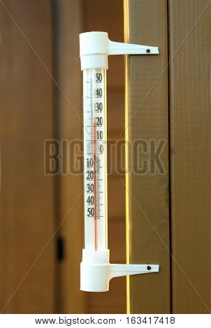 Outdoor thermometer showing 23 degrees Celsius, vertically hanging on a brown wooden wall of a house closeup