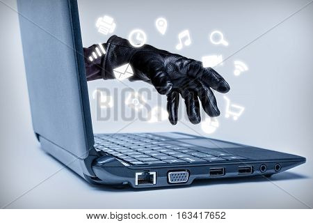 A gloved hand reaching out through a laptop with common media icons flowing signifying a cybercrime or Internet theft while using various Internet media. poster