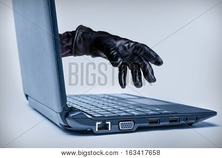 A gloved hand reaching out through a laptop signifying a cybercrime or Internet theft while using Internet media. poster