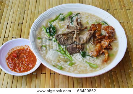 soft boiled rice with pork entrails on bowl and chili paste