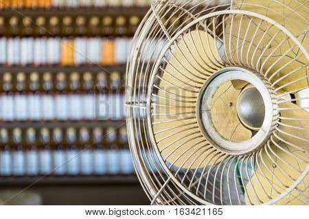 Dirtyand Old Vintage electric fan with rows of Bottles in background