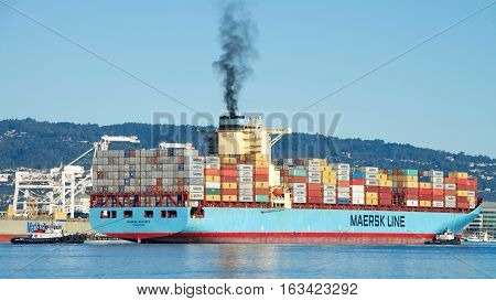 Oakland CA - December 28 2016: Multiple tugboats work in tandem to turn cargo ship MAERSK ANTARES prior to docking at the Port of Oakland.