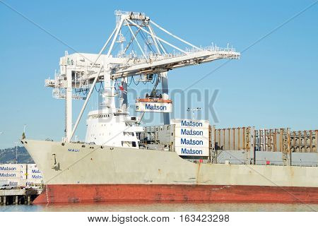 Oakland CA - December 28 2016: Matson cargo ship MAUI unloading at the Port of Oakland. Matson provides shipping services Pacific wide. Mainly to and from the Hawaiian Islands.