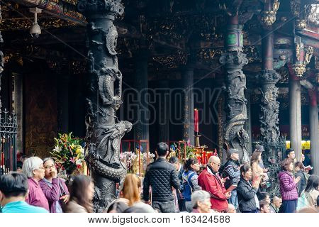 Taipei, Taiwan - Dec. 3 : Asia culture concept - people pray for god in famous heritage landmark the traditional old oriental Chinese temple lungshan with with beautiful dragon pillar decoration at Dec. 3 2016