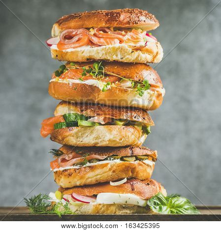 Heap of Bagels with salmon, eggs, vegetables, capers, fresh herbs and cream-cheese, grey concrete background, square crop. Healthy breakfast, lunch or take-away food concept