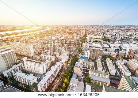 Business and culture concept - panoramic modern city skyline bird eye aerial view under dramatic sunset glow and beautiful cloudy sky in Tokyo Japan