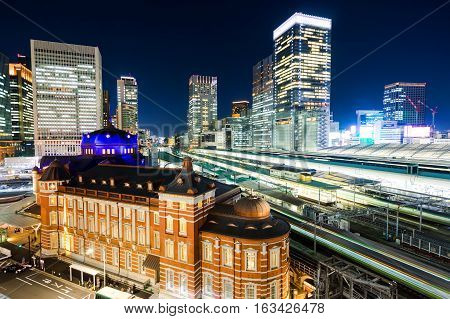 Business concept for real estate and corporate construction - panoramic modern city skyline bird eye aerial night view with tokyo station under dramatic glow and beautiful dark blue sky in TokyoJapan