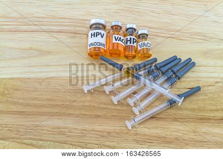 Bottle vaccine of Human papillomavirus (HPV) vaccine and disposable syringe on wooden background