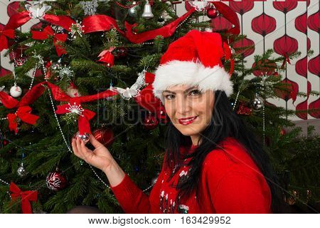 Beauty smiling woman with Santa hat in front of Christmas tree