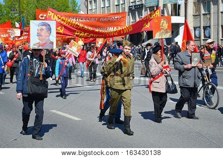 People with banners flagy and Stalin's portraits participate in demonstration in honor of the Victory Day on May 9 2016. Tyumen Russia