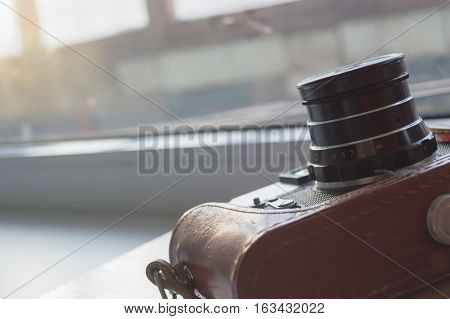 old photo camera in leather case with window on background