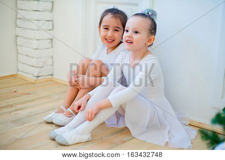 Two Young Ballet Dancer Sitting Near Christmas Tree