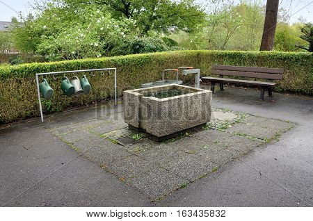 Fragment of park beautification. Concrete reservoir of water and cans for watering plants.
