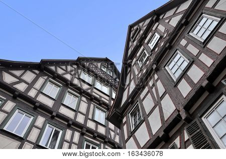 Look up at two old typical half-timbered houses of black frame and white stucco. Waiblingen, Baden-Wurttemberg, Germany.