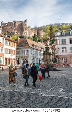HEIDELBERG, GERMANY - MAR 29, 2014: Tourists walking in the famous Marktplatz or Market Square in the old historical town of Heidelberg in Germany