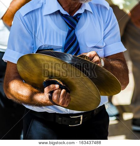 musician plays the cymbals during a religious procession