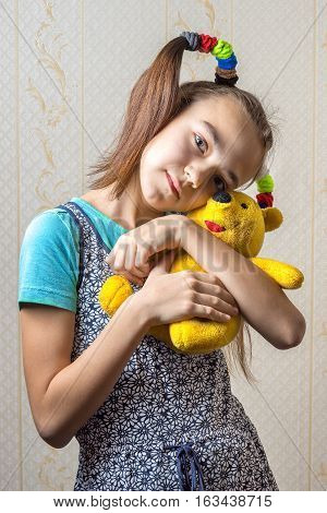 11 year old girl gently huggs her yellow toy bear