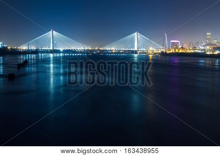 A view of the St. Louis skyline at night over the Mississippi River.