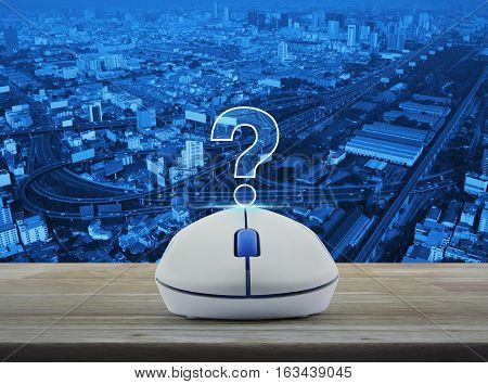 Wireless computer mouse with question mark sign icon on wooden table over city tower street and expressway Customer support concept
