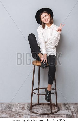 Full length portrait of a cheerful young girl winking and showing peace gesture while sitting on chair isolated on the gray background