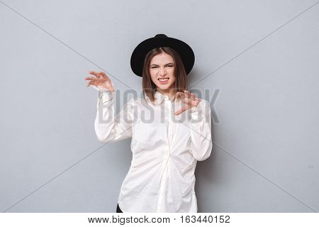 Portrait of an angry playful woman gesturing like cat claw isolated on a gray background