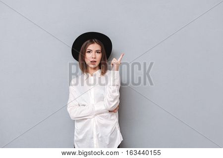 Portrait of an astonished brunette girl in hat and shirt pointing finger up isolated on a gray background