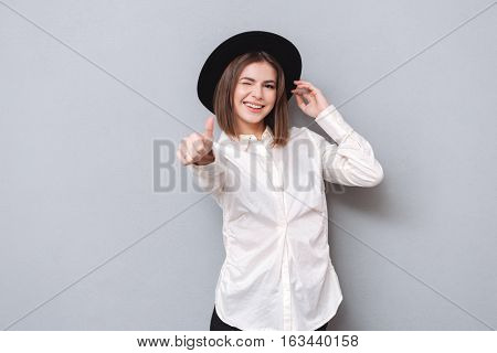 Portrait o a cheerful woman winking and showing thumbs up isolated on a gray background