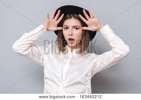 Portrait of an astonished excited woman holding hands at her face and looking at camera isolated on the gray background