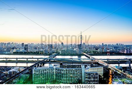 Business concept for real estate corporate construction - panoramic modern city skyline bird eye aerial night view with tokyo skytree under dramatic glow and beautiful dark blue sky in Tokyo Japan