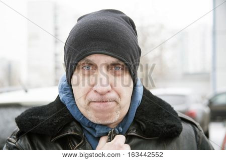 Head and shoulders outdoor portrait of a matured man wearing warm clothes