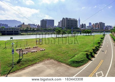 Riverside park cycling path and cityscape in Taipei