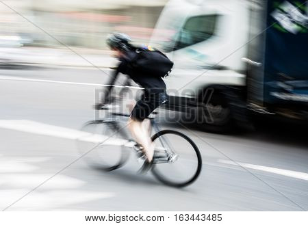 Bicycle Rider In City Traffic With Motion Blur