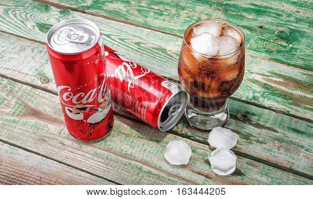 MINSK, BELARUS-DECEMBER 29, 2016: Glass of Coca-Cola with ice, can and bottle of Coca-Cola on wooden background. Coca-Cola is a carbonated soft drink sold in stores, throughout the world.