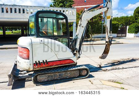 Mini excavator with narrow bucket for laying fiber-optic cable line