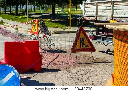 Warning signs for work in progress on road under construction. fiber optic cables buried in a micro trench with concrete colored red by a worker