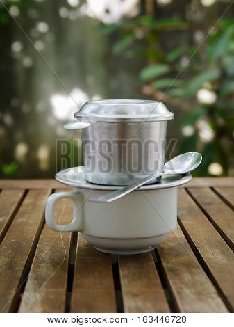 A cup of coffee with spool & filter above on a wooden table in garden