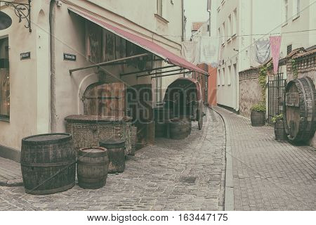 Barrels and vintage chests with medieval flags and standards on the stone narrow streets of Riga