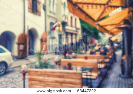 Street summer restaurant with yellow striped awnings in the historic center of Riga. Blurry