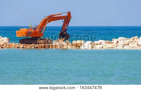 building the jetty with heavy excavator machine. Note the turbulence of the air emitted from the exhaust pipe of the excavator