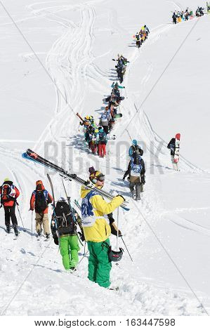 KAMCHATKA PENINSULA RUSSIA - MARCH 9 2014: Skiers and snowboarders climbing the mountain for freeride. Competition Kamchatka Freeride Open Cup. Eurasia Russian Far East Kamchatka Region.