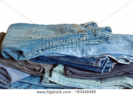 Pile of many colored jeans isolated on white background horizontal view close-up