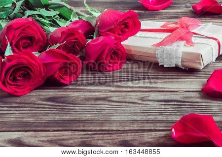 gift and red roses with petal on a wooden brown background
