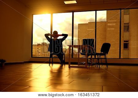 The concept of a business dream relaxation solutions. Businessman on  chair looking out window in modern office at sunset  sunlight.