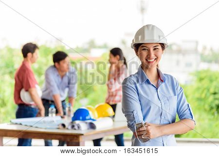 Asian beautiful engineer standing in front of their meeting group