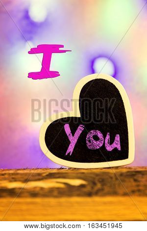 A heart in front of a colorful background with the inscription I love you