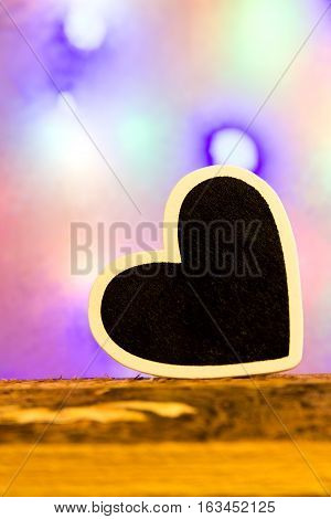A black heart in front of a colorful background on a wooden background