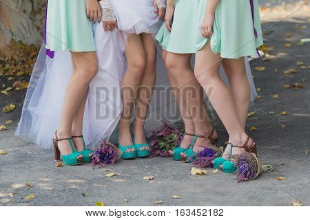 Legs of the bride and bridesmaids and flower bouquets. Wedding