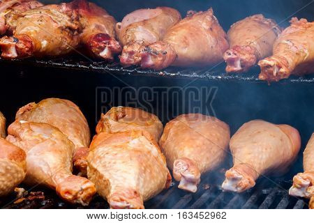 Close-up of appetizing turkey drumsticks on the grill with smoke. Concept summer picnic outdoors