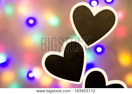 Two Black hearts against a lit background